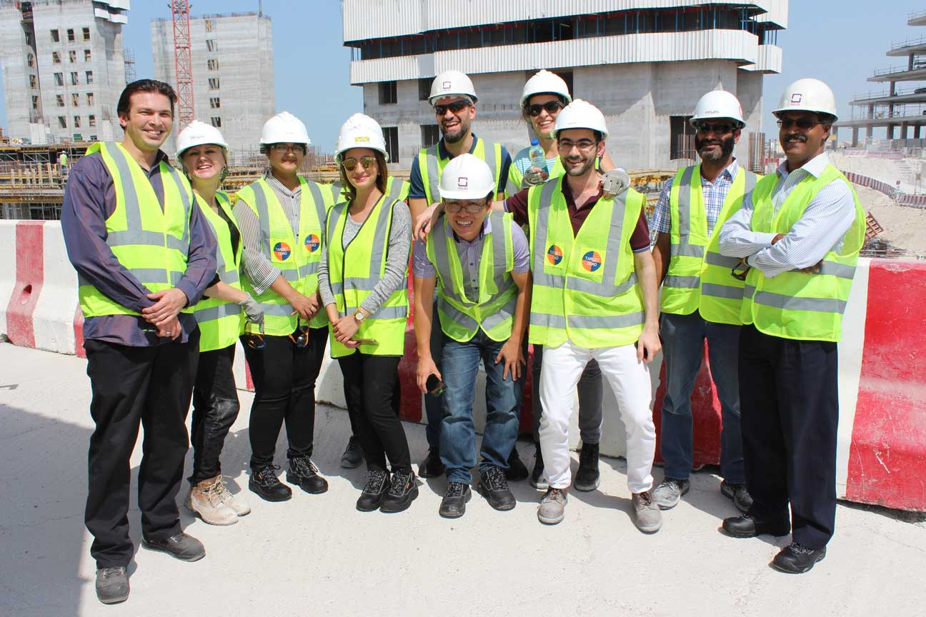 Group of people on construction site wearing white hard hats and fluorescent hi-vis jackets