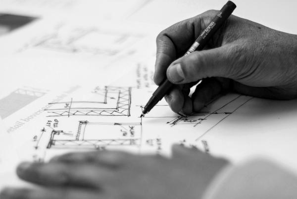 Hand holding black pen sketching building designs