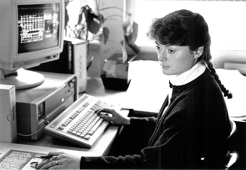 black and white photograph, woman with hair braid using old computer