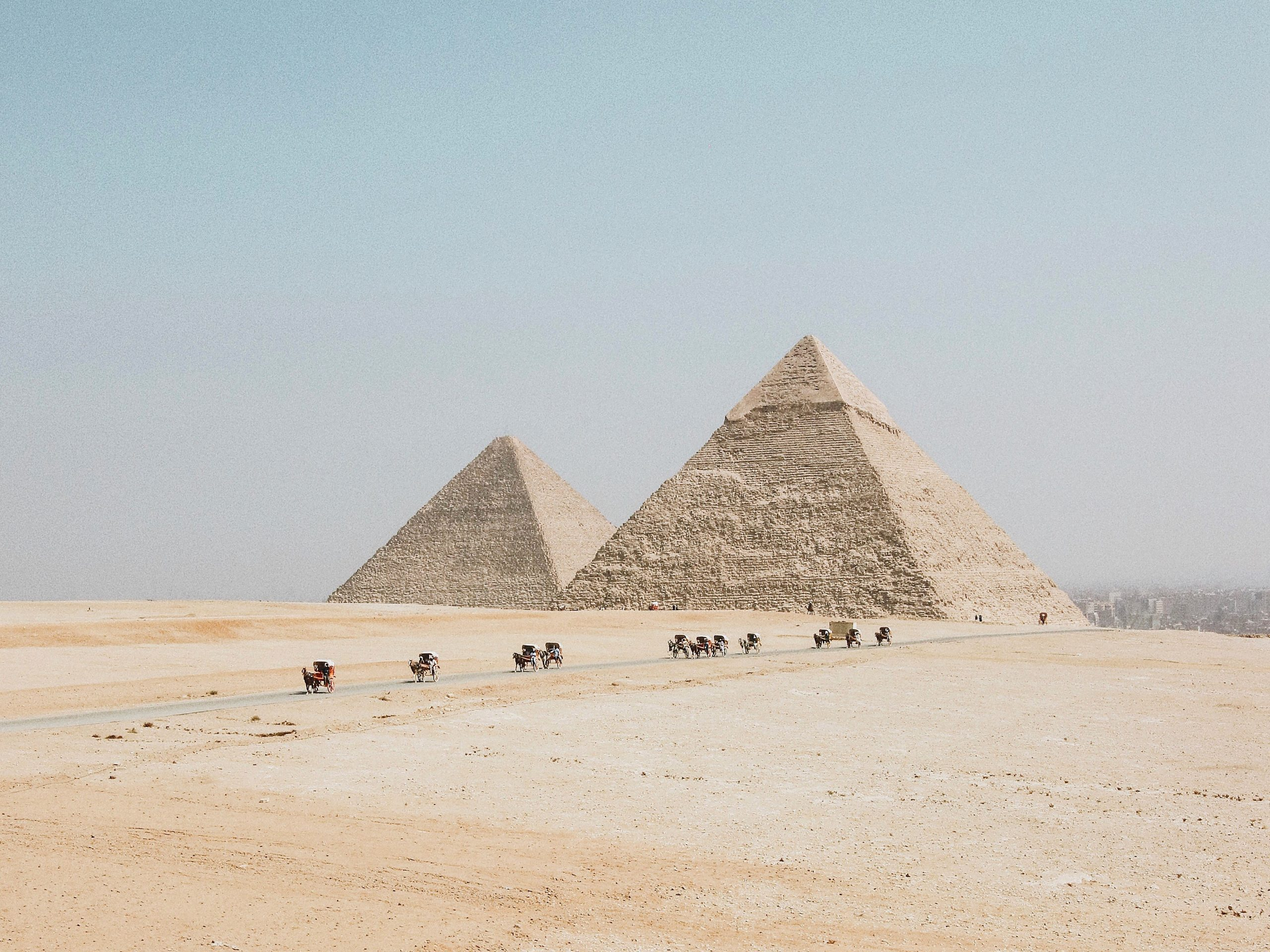 stone pyramids in desert, people and camels traveling on dirt road below