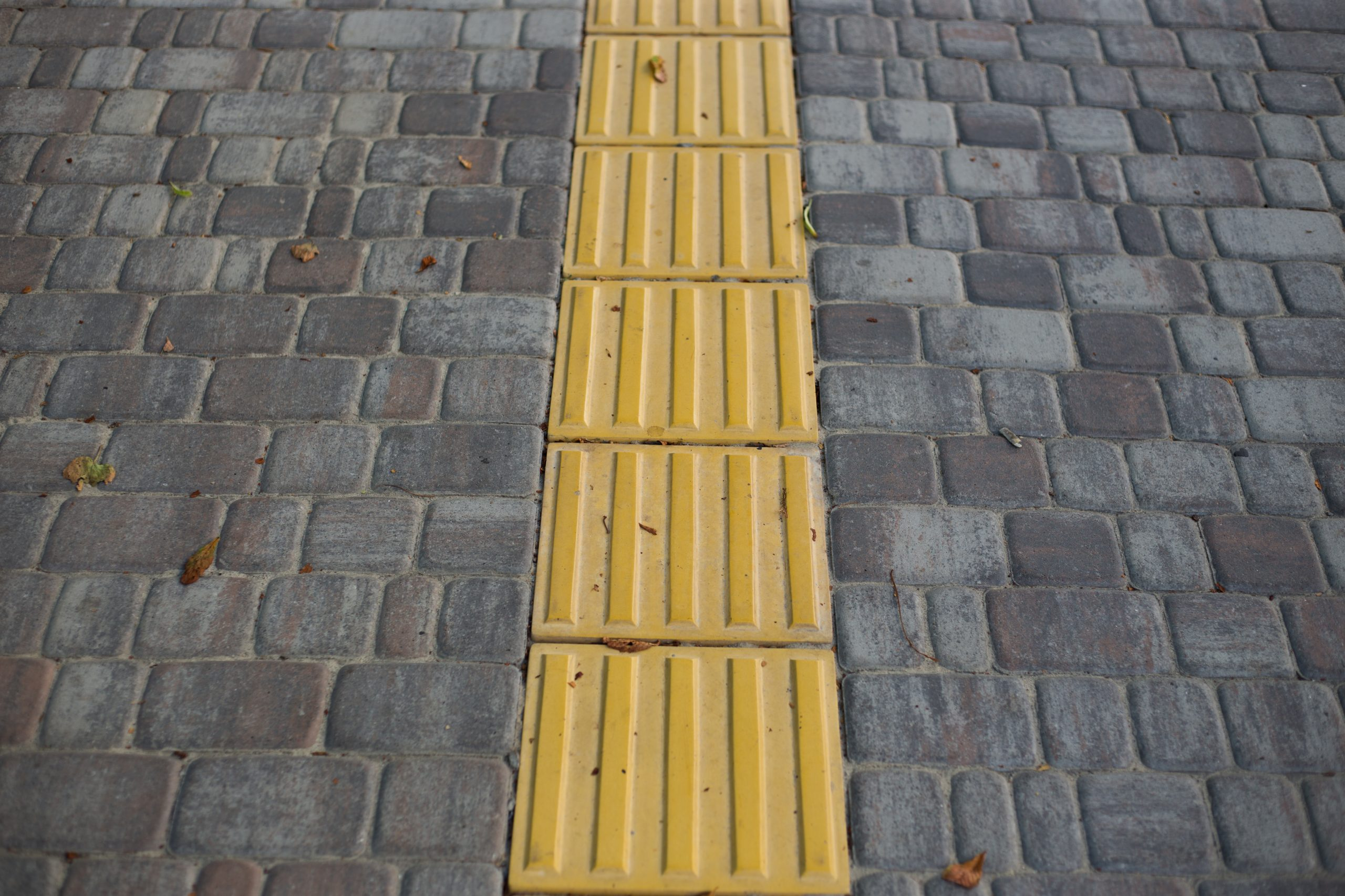 the picture shows a grey pavement. In the middle there are yellow warning tiles for visually impaired users.